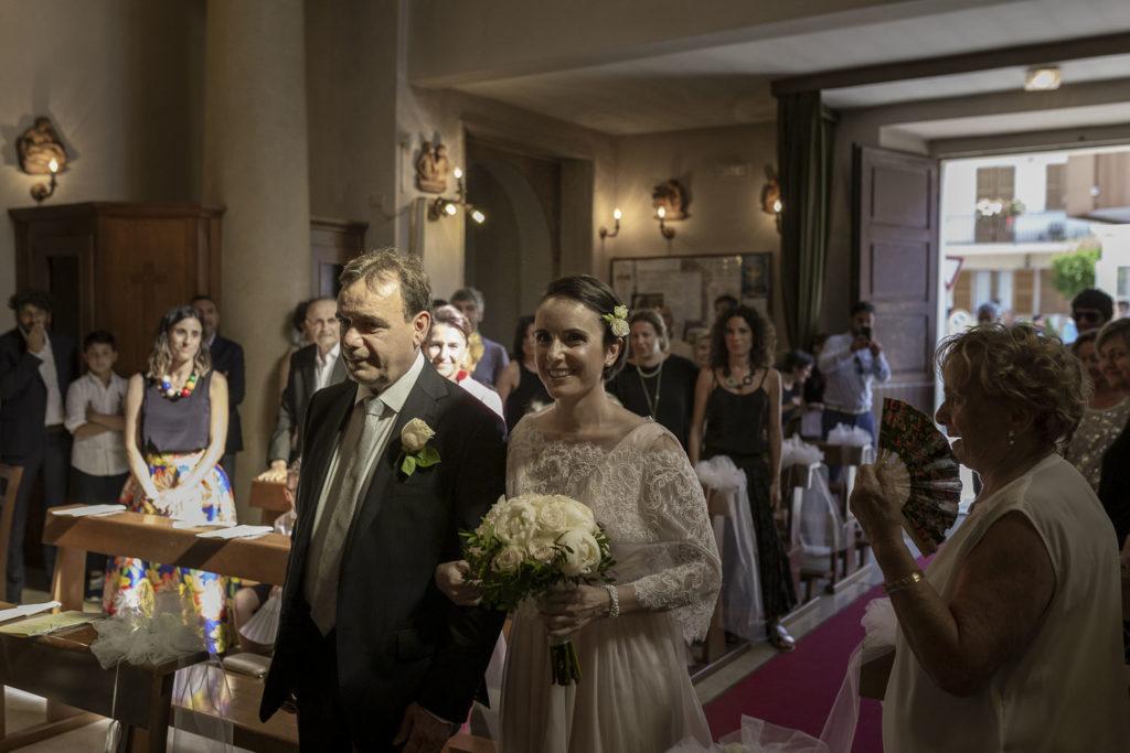 Matrimonio nelle Marche ingresso in chiesa della sposa con bouquet