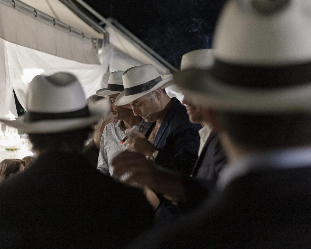 Amici dello sposo con cappello panama e sigaro cubano durante il party